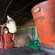 CAPTION: Bhalo Devi lugs a bag of biomass up to the hopper of one of DESI Power's gasifiers for combustion. LOCATION: Behirban, Araria District, Bihar, India. INDIVIDUAL(S) PHOTOGRAPHED: Bhalo Devi.