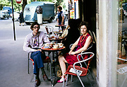 People sitting outside at street cafe table, city centre of Paris, France in 1970