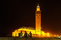 Silhouettes of people in front of Hassan II Mosque at night,  Casablanca, Morocco