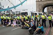 Environmental activists from Extinction Rebellion sit on Tower Bridge during an Impossible Tea Party event after it was blocked using a caravan on 30th August 2021 in London, United Kingdom. Extinction Rebellion were drawing attention to financial institutions funding fossil fuel projects whilst calling on the UK government to cease all new fossil fuel investment with immediate effect on the eighth day of their Impossible Rebellion protests in London.