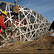 """Construction workers in Beijing build the """"Bird's Nest"""" National Stadium, which will be unveiled for the 2008 Summer Olympics."""