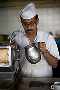 A barista warms milk for coffee from an ancient espresso machine in the Indian Coffee House, Baba Kharak Singh Marg, New Delhi, India.The Coffee House dates back almost fifty years, first in central Connaught Place, then Janpath and now at the top of a rather shabby shopping centre. Still run by the Indian Coffee Workers Cooperative Society, it was a regular haunt for politicos in Delhi and It's clientelle is still well read and intellectual.