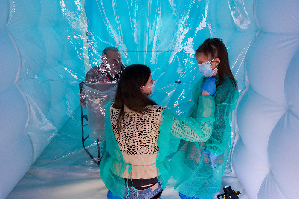 A mother and her daughter wearing protective suits against the spread of the novel coronavirus COVID-19 meet a relative through a plastic sheet installed in a special 'hug room' organised to keep people safe from COVID-19 infection at a care home in Santa Lucia di Serino, province of Avellino, southern Italy, on January 2, 2021.