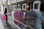 Bus passengers await the next service at a bus stop in Kingston-upon-Thames, on 12th November 2020, in London, England.