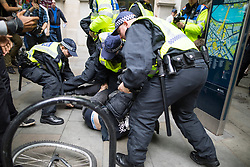 """© Licensed to London News Pictures . 24/06/2017. London, UK. Police detain an anti fascist on Northumberland Avenue . The English Defence League ( EDL ) hold a March on Parliament , from Charing Cross to Victoria Embankment , opposed by  a counter demonstration by Unite Against Fascism . Scotland Yard said it was using public order laws to restrict the marches """"due to concerns of serious public disorder, and disruption to the community"""" following terrorist attacks in Manchester , Westminster and Finsbury Park and the Grenfell Tower fire  . Photo credit: Joel Goodman/LNP"""