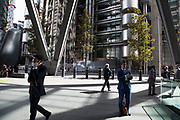 City workers passing by outside the Lloyds Building in the City of London, England, United Kingdom. The Lloyds building also sometimes known as the Inside-Out Building is the home of the insurance institution Lloyds of London, and is located at 1, Lime Street. It was designed by architect Richard Rogers and built between 1978 and 1986. The building was innovative in having its services such as staircases, lifts, electrical power conduits and water pipes on the outside, leaving an uncluttered space inside.
