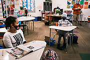 17 FEBRUARY 2021 - DES MOINES, IOWA: Socially distanced 4th grade students at Walnut Street School in downtown Des Moines. Des Moines Public Schools (DMPS) opened to in person education this week after teaching most of the 2020-2021 school year either remotely or with a hybrid/remote learning model. Elementary school classrooms, which used to sit 2-4 students at a table, have gone to individual desks, placed 6 feet apart, in classrooms. Students are required to wear masks for most class activities. The district has ended its hybrid model. The Governor of Iowa has aggressively pushed schools to return to in person education, going so far as to threaten to withhold funds from districts that don't return to in person classes. DMPS, the largest school district in Iowa, has resisted the Governor's push because Polk County, IA, has been a Coronavirus/COVID-19 hotspot with positivity rates well above 10 percent. The district was recently able to vaccinate many teachers and positivity rates have fallen to 9 percent, making it safer to reopen schools.     PHOTO BY JACK KURTZ