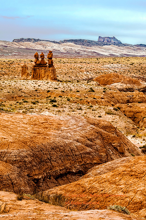 Surreal River Valley: The surreal view of a dried river valley, with the coloured mountains off in the horizon, winding through the orange coloured first valley, in Goblin State Park - Utah USA.