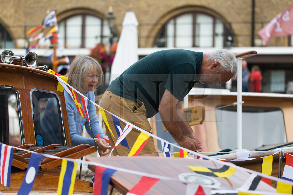 © Licensed to London News Pictures.  03/09/2021. London, UK. Andrew Clements with his wife Jane work on their boat called Glitterwake at St Katharine Docks on the River Thames ahead of the Classic Boat Festival this weekend. With 40 vintage sail and motor yachts, the Classic Boat Festival is part of Totally Thames' 25th festival. Photo credit: Marcin Nowak/LNP