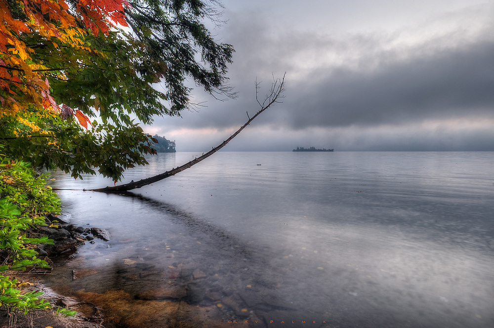 Lake George, Adirondacks, NY.<br /> There's often not much room to see anything on the lake's shores, other than the opposite side, because of the way the forest crowds the shoreline.  But a little scene unfolded while I explored, shooting up the water and including this near shore.  The atmosphere lent a hand, removing the distance and distraction.  With a little drama, the image became more intimate, animating the snag that appears to be reaching for meaning in that sky, while the nearer trees seem to reach for the wayward son.   Behind the backdrop, even the reach of the lake is indeterminate. In this dimension, it is hard to tell the feel--anger in an approaching storm, the sadness of a dreary day, or maybe the hope of a sunrise?  I let you reach your own conclusions.  Things are not always as they seem.