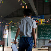 A fourth grade student goes to hand in his assignment at the front of his classroom in the floating village of Chong Kneas, just outside of Siem Reap, Cambodia.