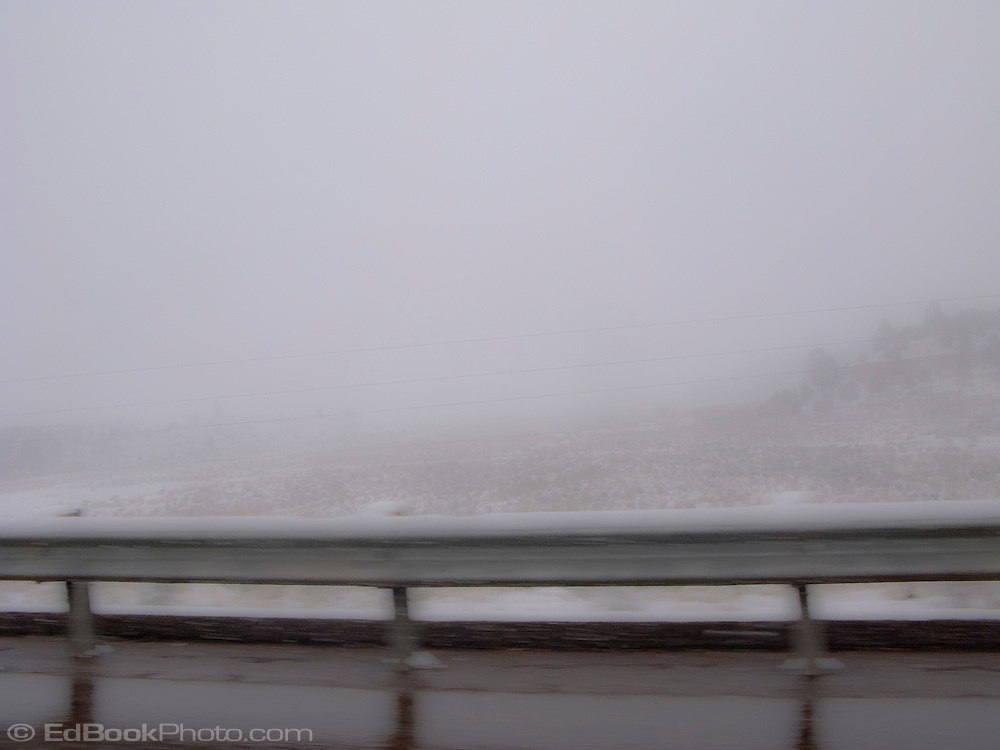 A guardrail stands out in contrast to unseasonable snowy weather along US 550 near the Continental Divide in NW New Mexico, USA  panorama