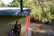 """CLIENT: THE WASHINGTON POST<br /> <br /> Marta Marbella Valencia, 32, and her daughter Angela Cristela, 2, stand under the eaves of their home in the in the village of El Verano in the Sierra Madre mountains in Mexico's Durango state. They were home alone in the early evening of October 6, 2015, when Marine helicopters descended and released a hail of bullets, some of which came through the roof. They hid first under the eaves, then in the bathroom and finally under a bed in the bedroom.  The military had been searching for Joaquin """"El Chapo"""" Guzman, the head of the Sinaloa cartel, who was rumored to have a home in the region."""