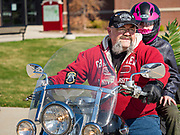 "05 APRIL 2020 - DES MOINES, IOWA:  BYKRMARK CARVER, and his daughter, ride Carver's motorcycle after a drive through Palm Sunday service sponsored by Luther Memorial Church on the campus of Grand View University in Des Moines. About 150 people attended the service. They remained in their cars while the ministers read a short passage from the Bible, handed out palms and blessed them. On Sunday, 05 April, Iowa reported 868 confirmed cases of the Novel Coronavirus (SARS-CoV-2) and COVID-19. There have been 22 deaths attributed to COVID-19 in Iowa. Restaurants, bars, movie theaters, places that draw crowds are closed until 30 April. The Governor has not ordered ""shelter in place"" but several Mayors, including the Mayor of Des Moines, have asked residents to stay in their homes for all but essential needs. People are being encouraged to practice ""social distancing"" and many businesses are requiring or encouraging employees to telecommute.       PHOTO BY JACK KURTZ"