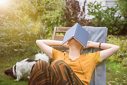 Beautiful young woman covering her face with a book and relaxing in the domestic garden, Munich, Bavaria, Germany