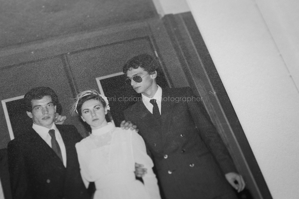 """CASTELVETRANO, ITALY - 17 FEBRUARY 2020: The wedding album of Giuseppe Cimarosa's parents, Lorenzo and Rosa (center), posing for a group picture with mafia boss and fugitive Matteo Messina Denaro (right) in Castelvetrano, Italy, on February 17th 2020.<br /> <br /> Giuseppe Cimarosa (36) was born into a Mafia family. He is a relative of Matteo Messina Denaro, Italy's most wanted Cosa Nostra godfather, on the run since 1993. Furthermore, investigators have long believed that Giuseppe's father, Lorenzo, occasionally provided """"support"""" for the fugitive godfather. """"My mother is a first cousin of Matteo Messina Denaro and my father was arrested as part of the Eden investigation [involving Messina Denaro]. I live in Castelvetrano [Messina Denaro's home town in Sicily, near Trapani] and I'm having a hard time . . ."""", Mr Cimarosa said.<br /> <br /> When the police came to arrest his father in 2013, Giuseppe was furious. There and then he wanted to again leave Sicily and return to Rome where he had lived and worked with horses for eight years in his 20s. He was disgusted that his father had again fallen into the clutches of their powerful relative. It was only when he went to visit his father in prison, immediately after his arrest, that Giuseppe changed his mind. In tears, his father told him that he was going to collaborate with the investigators, which he subsequently did. Realising how much his father was now risking, he opted not just to stay in Castelvetrano but also, in a certain sense, to fight back against the Mafia. What is more, he does so, not with a false identity as part of a witness protection programme, but rather by staying in his home town. His father, Lorenzo Cimarosa, died of cancer in 2017.<br /> <br /> Described as """"the last Mohican of the old mafia"""", Matteo Messina Denaro (57) is one of the world's most wanted fugitives, who has been in hiding since 1993. He was once considered a candidate to be the Sicilian mafia's boss of bosses after the deaths of Be"""