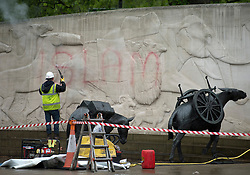 © London News Pictures. 28/05/2013. London, UK. A war memorial on Park Lane in London which was defaces with 'Islam' graffiti, being cleaned by a council worker on May 28, 2013. The word 'ISLAM' was written in red pint across one section of the memorial and wording on the stone memorial was crossed out. Photo credit: Ben Cawthra/LNP
