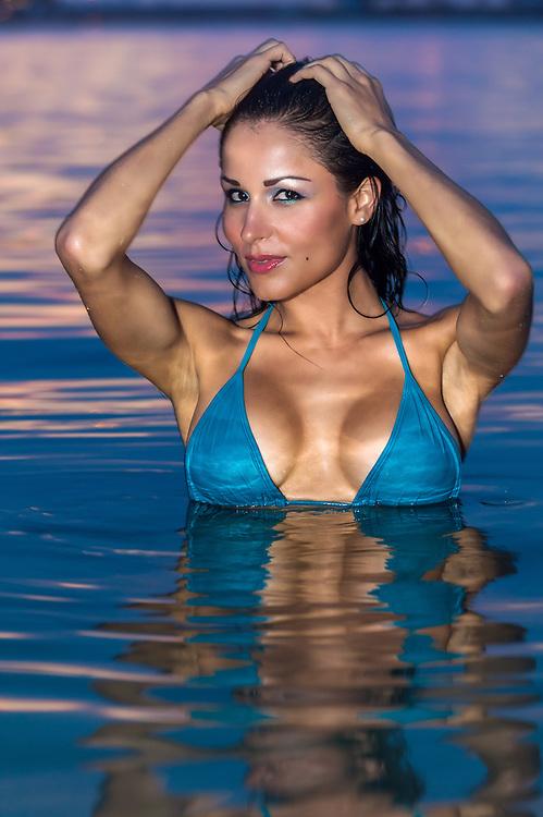 Young hot woman in blue bikini bra posing in the ocean during sunset