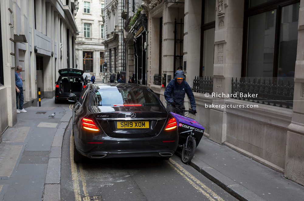 A bike courier squeezes past a black Mercedes in a narrow lane in the City of London, the capital's financial district, founded by the Romans and whose small lanes still date from medieval times, before the Great Fire of London in 1666, on 4th February 2020, in the City of London, England.