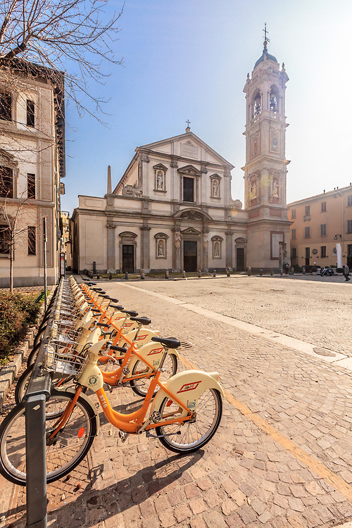 The communal bike sharing station in front of Basilica di Santo Stefano Maggiore in Milan, Italy. The bike sharing service offers citizens and tourists low-cost access to bicycles within the city to ease traffic congestion, curb pollution and boost physical activity.