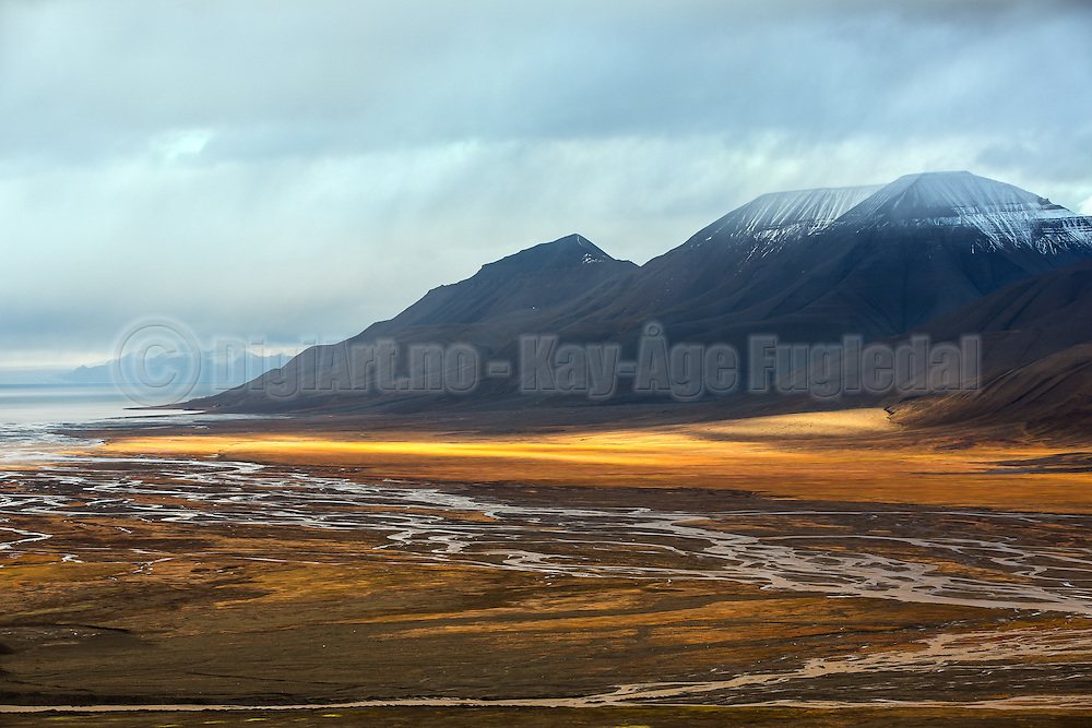 Early morning photo shot in Adventsdalen, Spitsbergen, with sunbeams by the foot of the Opera montain | Fotografering tidlig en morgen i Adventsdalen på Svalbard, med solstråler ved foten av Operafjellet.