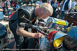 Thomas Trapp signs a Cannonball bike during Stage 16 (142 miles) of the Motorcycle Cannonball Cross-Country Endurance Run, which on this day ran from Yakima to Tacoma, WA, USA. Sunday, September 21, 2014.  Photography ©2014 Michael Lichter.