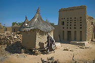 A dogon chief walking past a granary carries millet beer in a calabash container, Djigibombo, Dogon country, Mali.