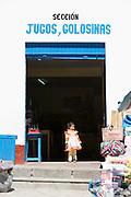 Girl standing in shop in Paucartambo, Cusco Region, Peru, South America