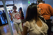 17 OCTOBER 2013 - PHOENIX, AZ:  Protesters go through security as they walk into the offices of the Arizona Attorney General. About 100 people came to the office of Arizona Attorney General Tom Horne to protest the decision by Horne to sue community colleges in Maricopa County that charge DREAM Act students who are residents of Arizona out of state tuition rather than in state resident tuition. Nearly 10 people were arrested in a planned civil disobedience during the protest.     PHOTO BY JACK KURTZ