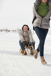 Woman dragging man on sledge in snow, Bavaria, Germany