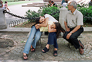 Tired from the heat:  Digvi Kapasi (15), left, and her sister Grishma (19), of Monmouth Junction, New Jersey, take a nap during a hot and humid afternoon on Central Park South, Monday, July 10, 2000.  The Kapasi's father, Rasesh, right, brought them into New York for the day to apply for visas to India.