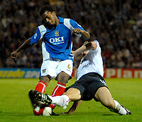 Photo: Ed Godden.<br /> Portsmouth v Bolton Wanderers. The Barclays Premiership. 25/09/2006. Portsmouth's Manual Fernandes(L) is brought to the ground by Kevin Davies.