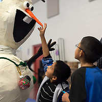 121714      Cayla Nimmo<br /> <br /> Jaydan Declay plays with the Olaf decoration at the Marine Corps Reserve Toys for Tots event held at the Zuni Wellness Center Wednesday.