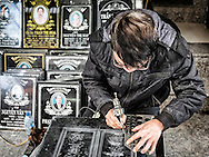 A man engraves designs in a tombstone at a shop along Hang Mam 'tombstone street' in Hanoi's Old Quarter, Vietnam, Southeast Asia