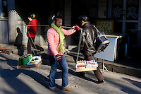 A young chinese woman goes to work selling dried fruits in the Beijing District of Qianmen South of Tiananmen Square on Monday 05 December 2005.