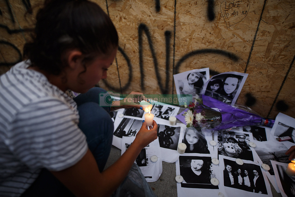 Friend of 18-year-old Danforth shooting victim Reese Fallon, Deja Shapiro, 21, leaves a candle on pictures of her friend Reese at a makeshift memorial remembering the victims of a shooting on Sunday evening on Danforth, Ave. in Toronto, ON, Canada, on Monday, July 23, 2018. Photo by Mark Blinch/CP/ABACAPRESS.COM