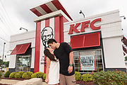 New Zealand Newlyweds Louis and Ashleigh Davis recreate their wedding photo Thursday, June 23, 2016 at a KFC in Louisville, Ky. The pair were given a trip KFC's hometown after their wedding photo at a Whangarei, New Zealand, KFC gained international attention in February. (Brian Bohannon/AP Images for KFC)