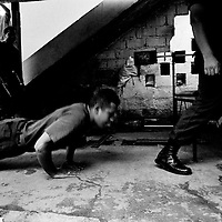Police officers workout in a makeshift gym in their fortress-like station.. Saravena is one of the most dangerous places in Colombia. The police station was attacked with homemade mortars 85 times in one year. Assassinations, sniper attacks and bombs are almost daily occurrences.<br />