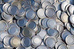 Close up of tin lids from cans which have been collected from a factory; sorted and are awaiting to be baled at a metal recycling centre,