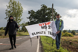Anti-HS2 activists carry a Stop HS2 banner along the Fosse Way on 24th August 2020 in Offchurch, United Kingdom. Environmental activists based at wildlife protection camps in Warwickshire have been trying to prevent or delay the felling of large numbers of trees in connection with the £106bn HS2 high-speed rail link, which will destroy or significantly impact many irreplaceable natural habitats including 108 ancient woodlands.