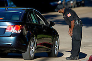 A security guard speaks with a driver at the apartment complex where a third Ebola patient lives in Dallas, Texas on October 15, 2014. (Cooper Neill for The New York Times)