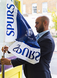 Estate agent Ercan Kucuk fixes a Spurs flag to his shop doorway ahead of Tottenham's Champions League final with Liverpool to be played at Atletico Madrid's Wanda Metropolitano Stadium in Madrid. Tottenham, London, May 29 2019.