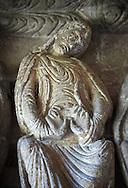 """Early Anglo Saxon sulpture of the an Apostle now part of the south porch of Malmesbury Abbey, Wiltshire, England. The apostles, apart from Peter who holds a crude key, have no distinguishing feature to allow identification. Some are holding books, none have halos and some hold their heads at awkward angles. These three styles are typical of Anglo Saxon art. The two panels are 10 ft long and 4ft 6"""" high are date from the original Ango Saxon church of 705. They were probablbly built into the proch during the Norman rebuilding. The style of these sculptures is of the Roman Byzantine style and were probably sculpted by masions from Gaul.  Malmesbury Abbey, Wiltshire, England"""