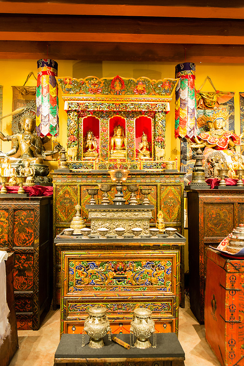 A nineteenth-century shrine cabinet (chosham) is at the center of the shrine room at the Rubin Museum, with a Tibetan offering table in the foregrund.
