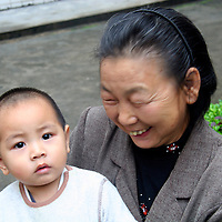 Asia, China, Guangxi, Daxu. A grandmother beams with pride as I ask to photograph her little one in the ancient town of Daxu.