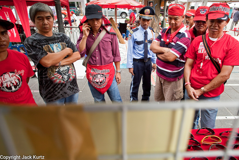 18 APRIL 2010 -- BANGKOK, THAILAND: People watch DVDs of the violence against Red Shirts at a Red Shirt stand selling DVDs and sunglasses near the protest site. The Red Shirts protest in the Ratchaprasong Shopping district, home to Bangkok's most upscale malls, is costing the Thai economy millions of Baht per day because the malls and most of the restaurants are closed and tourists are staying away from the area. But that hasn't stopped the Red Shirts who have brought their own economy with them. There are Red Shirt restaurants, food stands, souvenir vendors and more, creating a micro economy for Red Shirts in the area.  The Red Shirts continue to occupy Ratchaprasong Intersection an the high end shopping district of Bangkok. They are calling for Thai Prime Minister Abhisit Vejjajiva to step down and dissolve the parliament. Most of the Red Shirts support ousted former Prime Minister Thaksin Shinawatra.   PHOTO BY JACK KURTZ