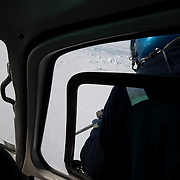 Dr. Steve Amstrup, leaning from a moving helicopter, takes careful aim with his dart gun used to inject immobilizing drug in to a polar bear. Beaufort Sea ice pack, Kaktovik, Alaska.