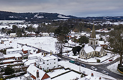 © Licensed to London News Pictures. 24/01/2021. Brockham, UK. Snow surrounds Christ Church (R) in the village of Brockham, Surrey. A band of snow is crossing the south east this morning as temperature remain just above freezing. Photo credit: Peter Macdiarmid/LNP