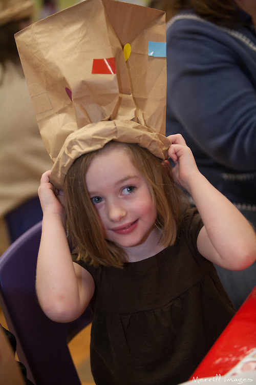 United States, Washington, Bellevue, girl (age 5) with paper bag hat at KidsQuest Children's Museum.  MR, PR