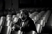 An opera singer takes a break, sitting in the auditorium seats before a performance.